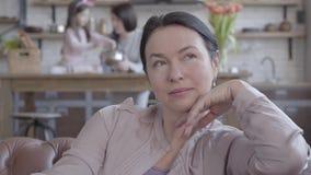 A mulher superior do retrato que senta-se no sofá, recorda dias passados com sorriso e agradecimentos No fundo é sua filha vídeos de arquivo