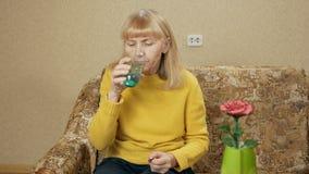 A mulher superior doente que tomam comprimidos na casa em um sofá e as bebidas molham em um vidro Faz a diversos o líquido liso E vídeos de arquivo