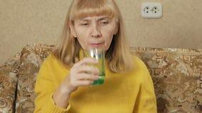 A mulher superior doente que tomam comprimidos na casa em um sofá e as bebidas molham em um vidro Faz a diversos o líquido liso E video estoque