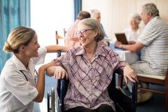 Mulher superior dos enfermos alegres que senta-se na cadeira de rodas que olha o doutor fêmea fotos de stock