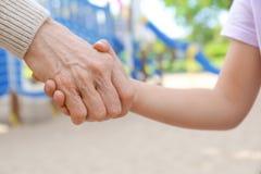 Mulher superior e criança pequena que guardam as mãos foto de stock