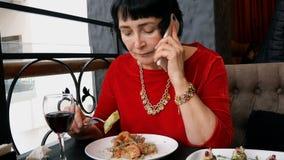 A mulher superior elegante no restaurante ou no café está comendo uma salada, bebendo o vinho video estoque