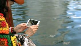 A mulher superior elegante toma fotos ou vídeos da água em seu smartphone video estoque