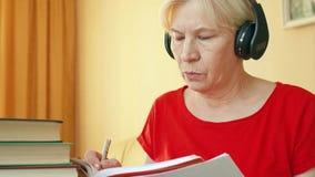 Mulher superior em fones de ouvido sem fio que treina as habilidades de escuta da língua estrangeira, escrevendo no livro de text filme