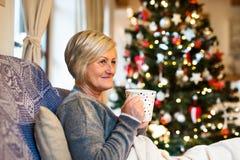 Mulher superior em Front Of Christmas Tree Imagem de Stock Royalty Free