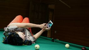 A mulher superior faz o selfie em seu smartphone, encontrando-se para baixo em uma mesa de bilhar em uma sala de bilhar filme