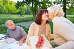A mulher superior felicita o amigo na festa de anos Imagem de Stock