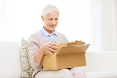 Mulher superior feliz com caixa do pacote em casa fotos de stock royalty free