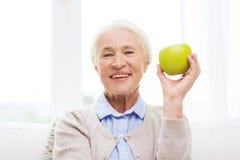 Mulher superior feliz com maçã verde em casa fotografia de stock