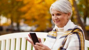 Mulher superior feliz com o smartphone no parque do outono vídeos de arquivo