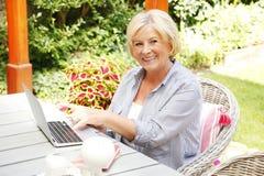 Mulher superior feliz com portátil fotos de stock