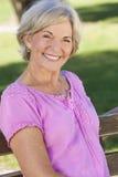 Mulher superior feliz do retrato que senta-se fora Fotos de Stock