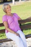 Mulher superior feliz do retrato que senta-se fora Imagem de Stock Royalty Free