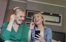 Mulher superior feliz e sua filha que escutam a música junto fotos de stock royalty free