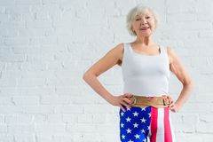 mulher superior feliz no sportswear que está com mãos na cintura e no sorriso imagem de stock royalty free