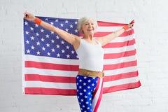mulher superior feliz no sportswear que guarda a bandeira americana e o sorriso imagens de stock royalty free