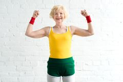 mulher superior feliz no sportswear que mostra os músculos e o sorriso fotos de stock royalty free