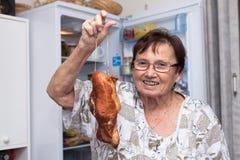 Mulher superior feliz que guarda a carne fumado Imagens de Stock