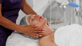 Mulher superior feliz que obtém a massagem da cara e do pescoço em termas fotos de stock royalty free