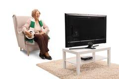 Mulher superior feliz que senta-se em uma poltrona com bola de futebol e w imagem de stock