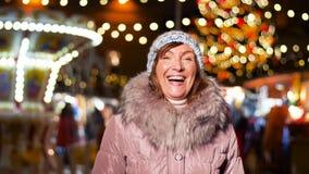 Mulher superior feliz que sorri no mercado do Natal filme