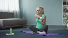 Mulher superior loura no sportswear que senta-se na esteira da ioga e que faz massagens seu ombro video estoque