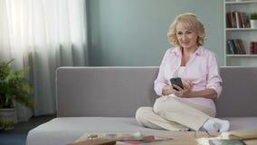 Mulher superior loura que paga as contas de serviço público em linha, usando o smartphone aplicações filme