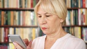 Mulher superior moderna em casa que usa o telefone celular, consultando, lendo Estantes da biblioteca no fundo video estoque