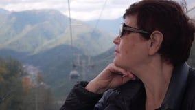 Mulher superior na cabine do teleférico que olha através da janela em montanhas video estoque