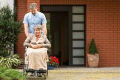 Mulher superior na cadeira de rodas apoiada pelo cuidador na frente da casa imagem de stock