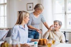 Mulher superior na cadeira de rodas com a família que senta-se na tabela em casa, bebendo imagens de stock royalty free