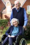 Mulher superior na cadeira de rodas que está sendo empurrada pelo marido Fotos de Stock Royalty Free