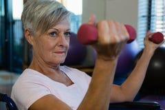 Mulher superior na cadeira de rodas que executa o exercício com o peso imagem de stock