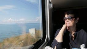 Mulher superior na camisa preta e nos óculos de sol que sentam-se perto da janela na cabine do trem filme