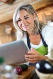 Mulher superior na cozinha que olha a tabuleta para a receita Fotos de Stock Royalty Free