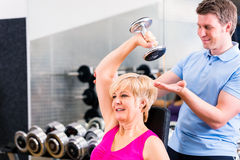 Mulher superior no exercício do esporte no gym com instrutor Imagens de Stock Royalty Free