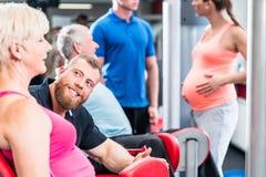 Mulher superior no grupo com a mulher gravida que dá certo no gym imagens de stock royalty free