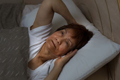 A mulher superior não pode dormir na noite devido à insônia Imagem de Stock