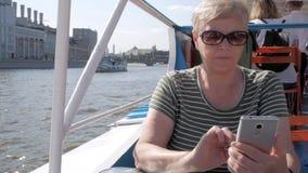 Mulher superior no smartphone da terra arrendada do barco de turista video estoque