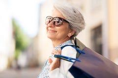 Mulher superior nos óculos de sol com sacos de compras fotografia de stock