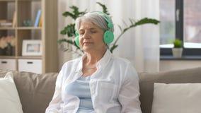 Mulher superior nos fones de ouvido que escuta a música video estoque