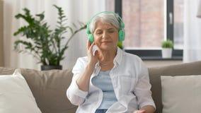 Mulher superior nos fones de ouvido que escuta a música filme
