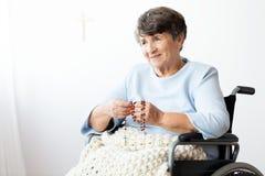 Mulher superior paralizada em uma cadeira de rodas que reza ao deus imagens de stock
