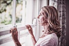 Mulher superior pensativa que olha para fora da janela imagens de stock