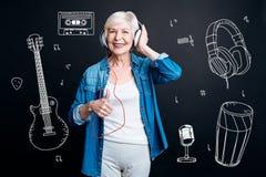Mulher superior positiva que coloca seu polegar ao escutar a música fotografia de stock