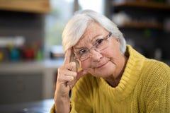 Mulher superior preocupada na cozinha foto de stock