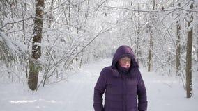 Mulher superior que agita a neve fora do revestimento do inverno na floresta do inverno video estoque