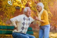 Mulher superior que ajuda o homem superior que tem uma dor nas costas fotos de stock royalty free