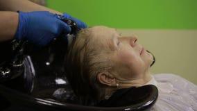 Mulher superior que aprecia o cabelo que lava no salão de beleza video estoque