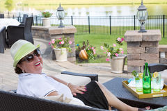 Mulher superior que aprecia uma bebida no terraço imagem de stock